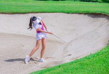 Thai Young Woman Golf Player In Action Swing In Sand Pit During Practice Before Golf Tournament At Golf Course