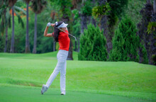 Golf Player Teeing Off. Woman Hitting Golf Ball From Tee Box With Driver..