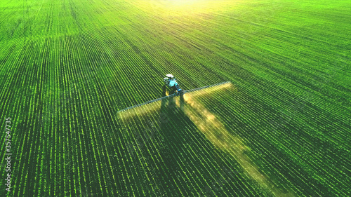 Fototapeta Tractor spray fertilizer on green field drone high angle view, agriculture background concept. obraz