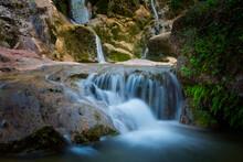 Waterfall Among The Creek Rocks In The Mountain