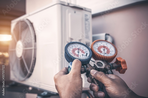 Fotografia Air repair mechanic using measuring pressure gauge equipment for filling home air conditioner after cleaners and checking maintenance outdoor air compressor unit