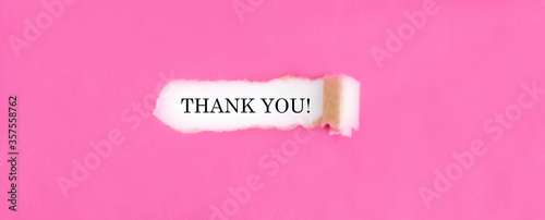 The text THANK YOU appearing behind torn pink paper.