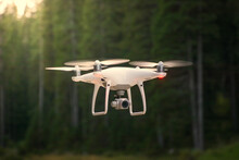 Drone Flying In Nature. Green Trees In Background. Low Angle, Shallow Depth Of Field