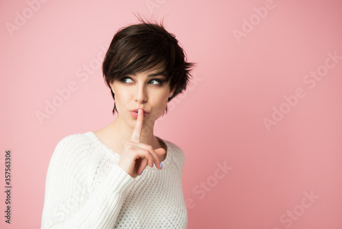 Beautiful young woman with long shot dark hair wears casual white sweater shows hush sign and looking up at left corner Canvas Print