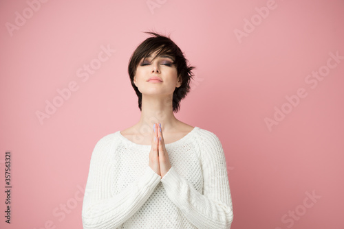 Fototapeta Young pretty woman praing with hands on chest and grateful gesture on face