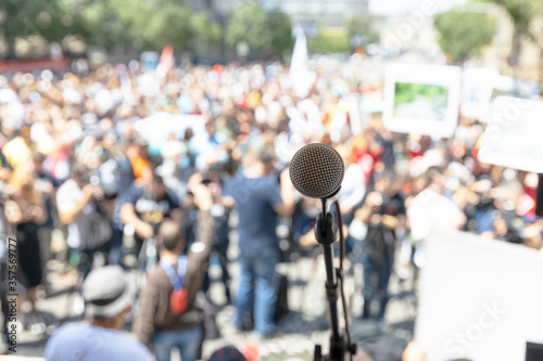 Photo Focus on microphone, blurred group of people at protest in the background