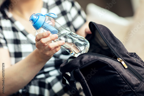 Fototapeta Woman takes the bottle out from backpack. Woman takes the reusable bottle of fresh water with carbon filter out from her backpack. obraz