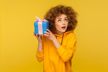 Portrait Of Funny Curious Curly-haired Woman In Urban Style Hoodie Holding Present Box Near Ear And Listening What's Inside, In Anticipation Of Dream Gift. Studio Shot Isolated On Yellow Background