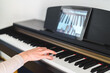 caucasian woman learning to play piano with video lessons. Concept of virtual learning