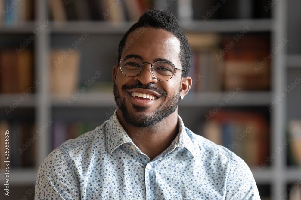 Fototapeta Head shot of african american bearded guy with pierced ear casual shirt smiling looking at camera standing indoor. Webcam view, conference video call, confident company representative portrait concept