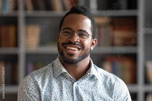 Fototapeta Head shot of african american bearded guy with pierced ear casual shirt smiling looking at camera standing indoor