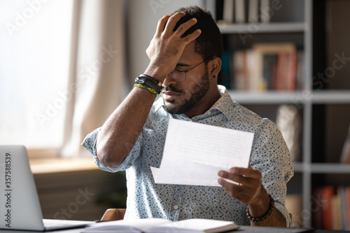Stressed african businessman sit at desk hold paper letter reading bad awful negative news got fired from work Canvas Print