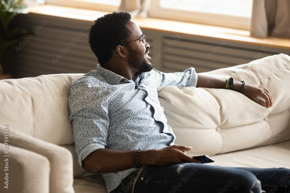 Fototapeta African calm guy seated on comfy couch in cozy light modern living room breath fresh conditioned air during warm summer day looking out the window daydreaming enjoy relaxation holding smart phone