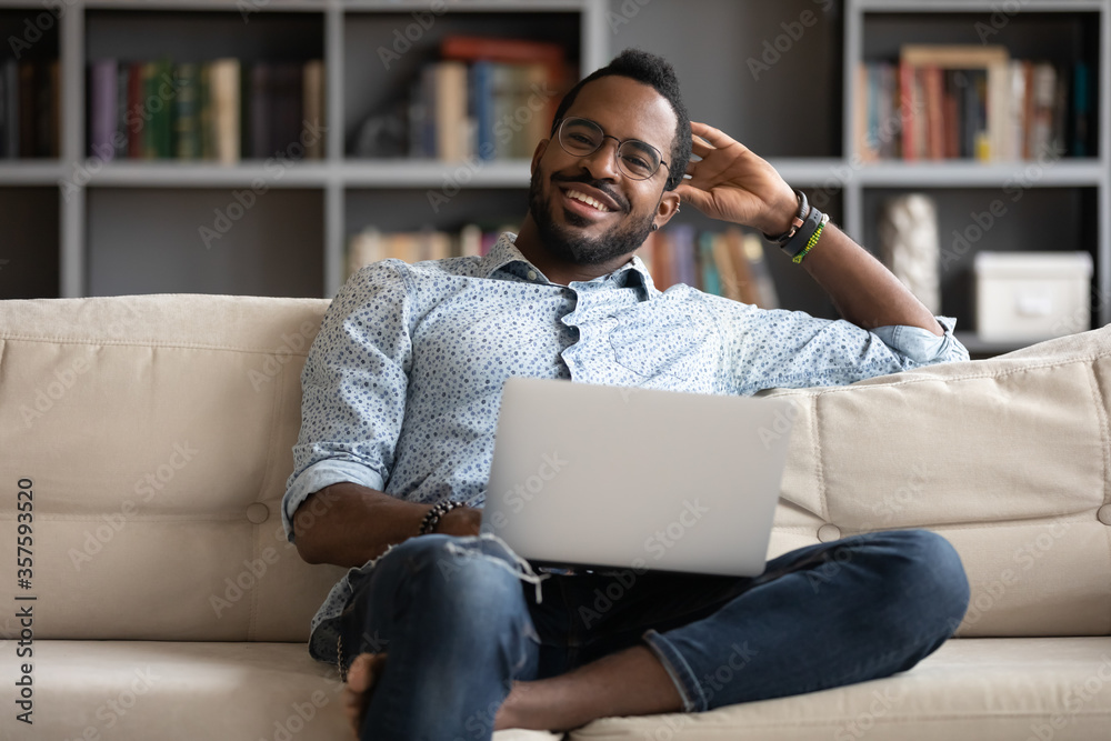 Fototapeta Smiling millennial African guy sit on couch in living room working on wireless pc from home, happy young man resting on sofa browsing internet shopping using computer, modern technology usage concept