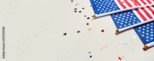 Festive background with US flags and confetti in the shape of stars. US independence day. Banner with copy space for text.