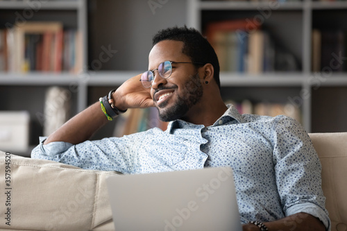 Fotografia African guy distracted from using laptop do remote work daydreams looking at window feels calm inner harmony enjoy fresh air and lazy day