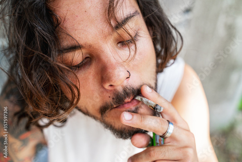 Obraz na plátne Young dark-haired attractive sexy mixed-race man smokes a cigarette, blows smoke