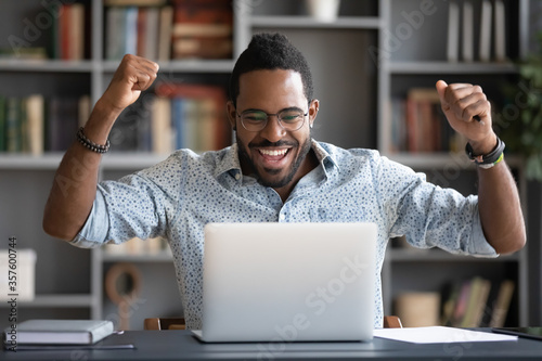 Leinwand Poster African guy feels happy received great news by internet looks at pc screen raise