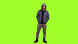 Leinwandbild Motiv Drug dealer standing with hands in pockets on green screen background, Chroma key front view