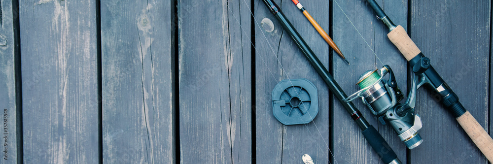 Fototapeta Fishing rods and reels on the wooden deck, fishing copy space