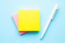 Bright Yellow And Pink Sticky Notes And White Pen On Light Blue Table Background. Pastel Color.  Empty Place For Message, Quote, Sayings Or Other Text For Positive Mood. Top Down View. Closeup.