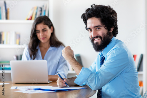 Cheering arabic businessman with female colleague Canvas Print