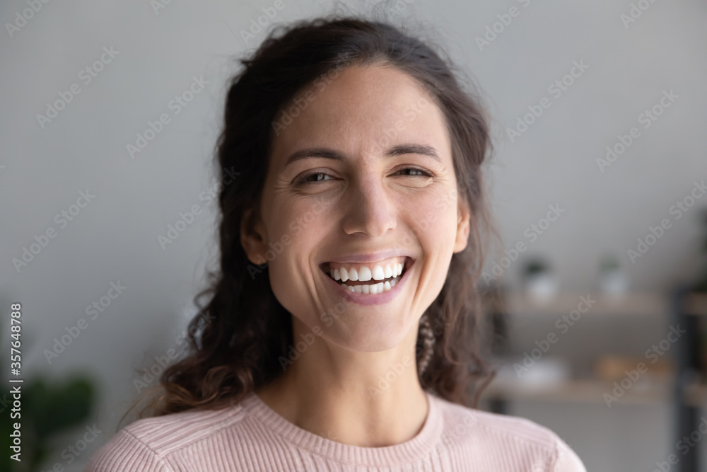 Fototapeta Head shot portrait close up laughing overjoyed beautiful woman with toothy smile looking at camera, making video call to friends or relatives, excited young female blogger recording vlog