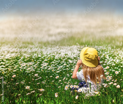 Happy little girl sits in the chamomile meadow dreamily looking at the sky and breathing fresh summer air enjoying tranquility, happiness and repose Canvas Print