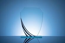 Elegant Blank Glass Shield Trophy On Dark Blue