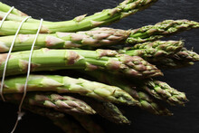 Photography Of A Bunch Of Green Asparagus Tied Like Market Gardeners On Slate For Food Background