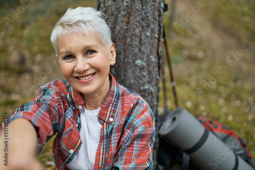 Fotografía Portrait of happy attractive middle aged woman with blonde hair sitting under pi