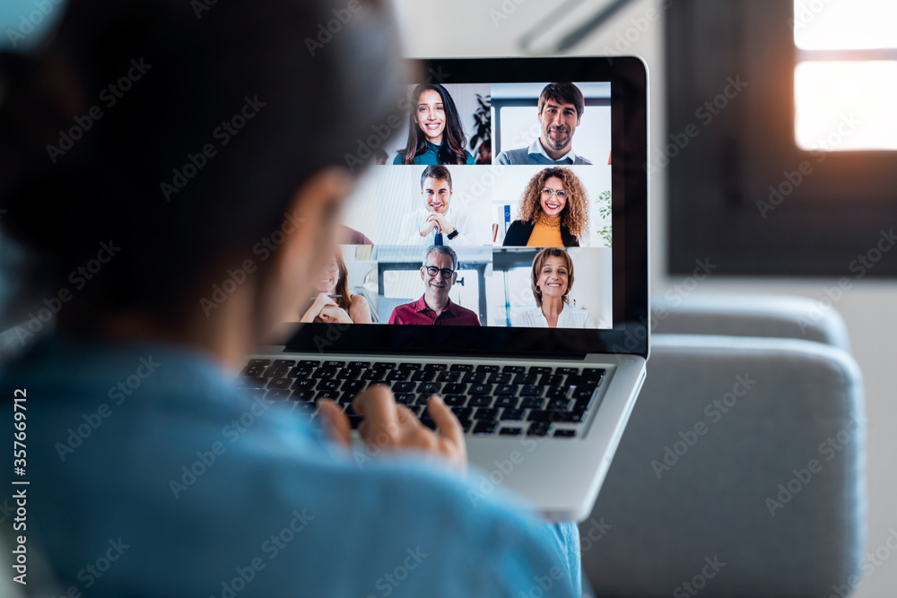 Fototapeta Business woman speaking on video call with diverse colleagues on online briefing with laptop on sofa at home.