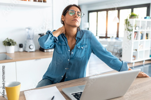 Fototapeta Tired business woman with neck pain looking uncomfortable while working from home on laptop