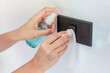 Thai woman wipes her hands with alcohol spray and towel washing switch. Coronavirus prevention for hand hygiene corona virus protection. COVID-19 prevention sanitizing inside.