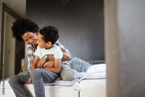 Fotografia Happy mother playing, having fun, hugging with her son at home