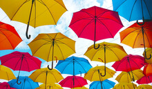 Colorful Umbrellas Hanging Overhead Over A Blue Sky
