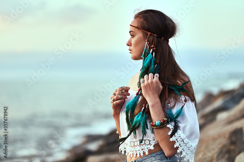 Portrait of attractive hippie woman wearing blue feathers in long hair, jewelry and white blouse at seashore Fototapete
