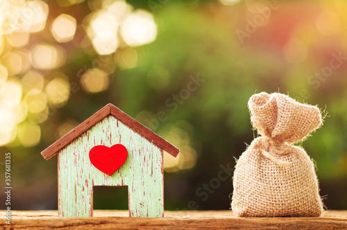 Wooden house model and money bag placed on wooden floor, Saving money for real estate with buying a new home and loan for prepare in the future concept Wallpaper Mural