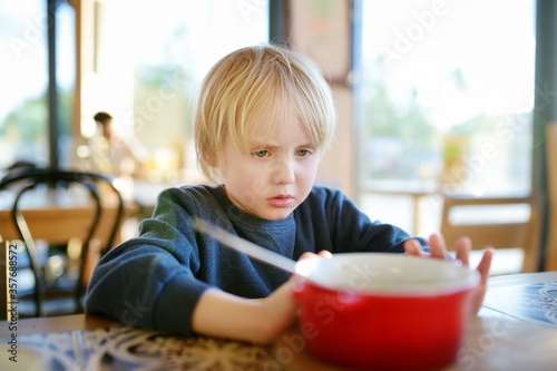 Little boy sitting the table in cafe or restaurant and doesn't want to eat Fototapete