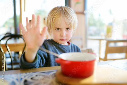Little boy sitting the table in cafe or restaurant and doesn't want to eat Tablou Canvas