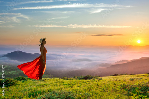 Fotomural Young woman in red long dress standing in morning mountains with rising sun and white fog below enjoying view of idyllic nature
