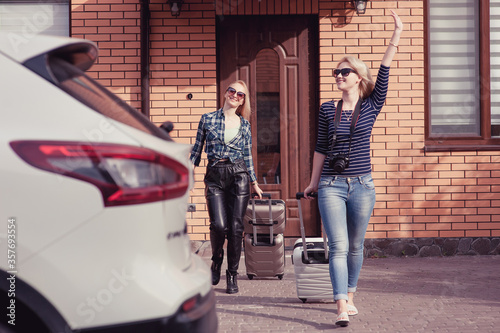 Fotografiet Two young women are going to travel by car