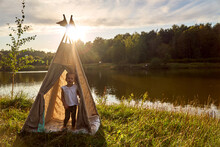 Girl At Sunset In Nature. Wigwam By The Lake. New Home In A Hut. CHILDREN'S GAMES. High Quality Photo