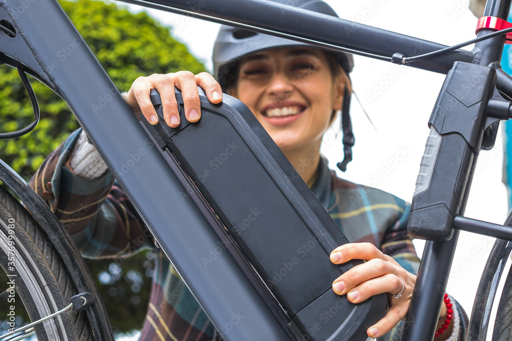 Fototapeta woman holding an electric bike battery mounted on frame
