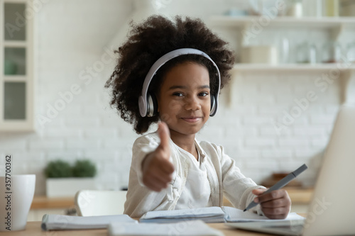 Fototapeta African girl in headphones enjoy e-learn sit at table showing thumbs up recommend e-study easy and interesting app for children, using modern tech