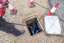 Man Unblocking Sewage Drain Through Open Inspection Chamber, UK