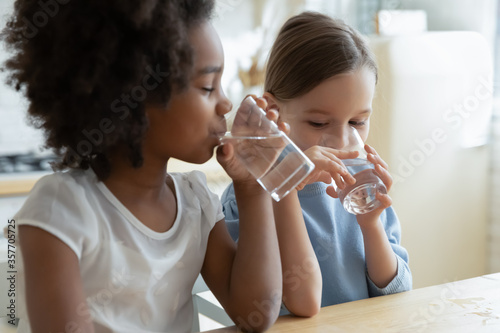 Fototapeta Two multi racial little girls sit at table in kitchen feels thirsty drink clean still natural or mineral water close up image