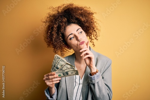 Obraz Young beautiful woman with curly hair and piercing holding dollars banknotes serious face thinking about question, very confused idea - fototapety do salonu