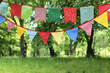 canvas print picture - Close up of bunting flags hanging among trees. Summer garden party. Outdoor birthday, wedding decoration. Midsummer, festa junina concept. Selective focus. Natural blurred background.