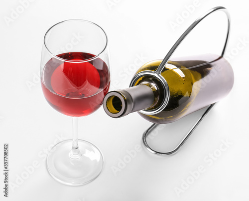 Obraz Holder with bottle and glass of wine on white background - fototapety do salonu